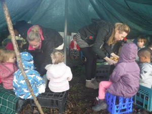 children in forest school shelter