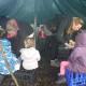 children in forest school shelter