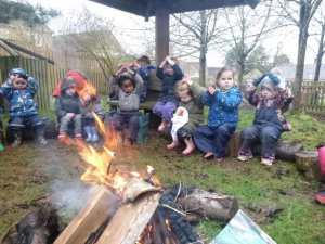 children sitting around campfire