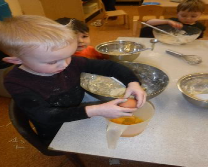 young boy breaking eggs