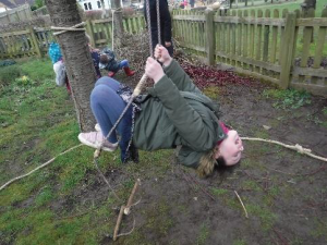 girl hanging on rope ladder outside
