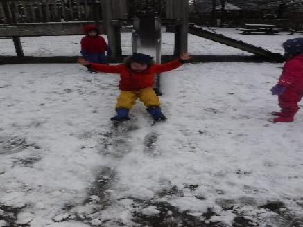 child on slide in snow