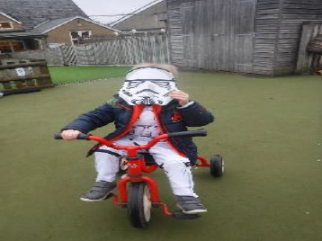 boy with mask on tricycle